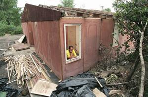Den romske aktivisten Josef Stojka i Ostrava i Tjeckien tittar ut genom fönstret på en barackliknande byggnad som fungerar som bostad för en romsk familj, vars hem har förstörts i en översvämning 1997. Arkivbild.