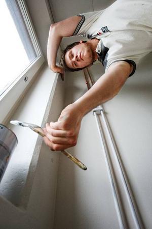 Johan Hellström-Reineke använder en liten elementpensel för målandet av vattenrören.  Foto: Ulrika Andersson