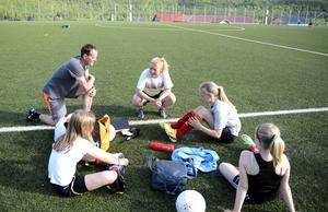 Fredrik Nyberg och Karin Stolt Halvarsson är barndomsvänner. Nu tränar de F02-laget, där båda har döttrar, tillsammans.