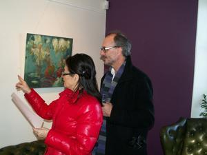 Färgstarka kontraster fanns också bland besökarna. Evy och Fredrik Meurman begrundar en av målningarna. Bild: Bob Engelbertsson.