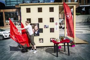 Nisse Sandkvist ställer ut campingbordet, vattnar blommorna och rättar till flaggorna vid Vänsterpartiets valstuga på Stortorget i Östersund.