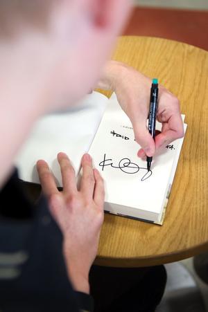 Kristian Gidlund signerar sin bok som kom ut i våras.