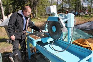 Dick Persson visar deras egenhändigt tillverkade brynsåg med sågklinga av diamant.