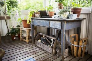 Ett gammalt skrivbord ger plats åt växterna i uterummet.