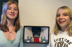 Viktoria Möller och Ellinor Strömberg står bredvid sin grupps tittskåp som föreställer Hotell Knaust.