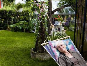 Få en fin trädgård är inget latmansgöra. Men då och då blir det tid över för en stund i hängmattan, för Ingrid Andersson. I bakgrunden skymtar ett växthus.