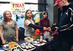 Åre skolas klass fyra passade på att dryga ut skolresekassan genom att sälja fika med hembakt bröd. Här gör Idun Edvardsson, Kim Olinder och Pelle Sahlberg affär med kommunens näringslivschef Janne Andersson.