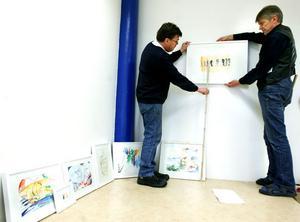 Per-Håkan Laurin och Hans Tjernström hjälps åt att visa upp Aljo Weijls akvareller.