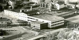 En flygbild över EIA som det såg ut innan Sandvik byggt på kontorsdelen med en våning och utökat produktionslokalerna åt väster. Till vänster syns den äldsta delen som byggdes på 1940-talet.