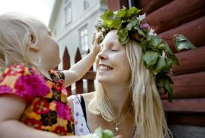 Annette Mattsson, 33 år, med dottern Signe Östlund, 2 år, Örebro.–Signe gillar prästkragar, och jag tycker om liljekonvaljer. Vi plockade blommor nere i Oset i går kväll, och så gjorde vi våra kransar i morse.