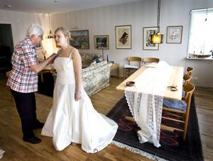 Britt Lagerqvist, 79, har sytt och designat kläder hela sitt liv. Här tar Britt emot Maria Jarlsmark i vardagsrummet för provning av brudklänning.