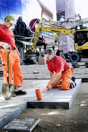 EN HÄLL I TAGET. Stensättarna Szymek Legutko och Wladyslaw Kapusta påbörjade på tisdagen arbetet med att sätta granithällarna på Stortorget i Gävle. Totalt 4 325 kvadratmeter eller 13 000 granitblock ska sättas för hand.