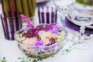 Vackra växter från naturen blir en del av dukningen, här har blommor som stämmer överens med dukningen färgskala placerats i en vacker glasskål.