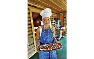 Julia Holm sommarjobbar. Här har hon precis bakat tigerkaka med grädde och jordgubbar på.-- Jag gick hotel- och restauranglinjen på gymnasiet och har lärt både där och här hos Anna-Karin.FOTO: BOEL FERM