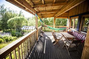 Uteplatsen med Rolfs hemmagjora snurrpinnar som spinner glatt i vinden. Med utsikt över Kallsjön och den stora lummiga trädgården sitter Eva och Rolf här ute så ofta de kan.