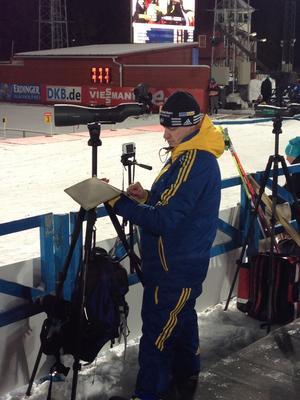Det är fullt upp för svenske tränaren Marko Laaksonen. Han följer skyttet i sin kikare och håller koll på ställningen i sin surfplatta.