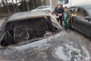 Salwan Sabry med barnen Sara och George vid en av de utbrända bilarna. Trots oroligheterna säger han att han trivs mycket bra i Hovsjö.