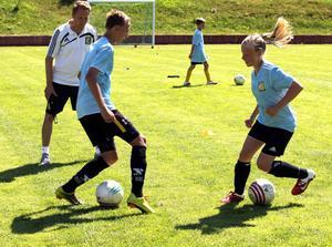 Mart Sundkvist-Box, 15, och Josefine Blom, 13, tränar på finter medan fotbollstränaren Anders Hermansoninstruerar på Åbyvallen i Valbo där det just nu hålls fotbollsskola för ungdomar.