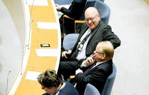 Ögonblicket då statsministern i riksdagen offentliggör Peter Hultqvist som ny försvarsminister, den 3 oktober. Bänkgrannen Ulf Berg (M) från Avesta gratulerar.
