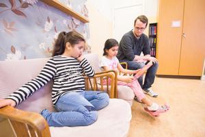 Malak Shanta och Alicia Lavanwalli tränar på läsning. Lärarstudent Tobias Wrammer från Borlänge stöttar dem när de behöver hjälp.