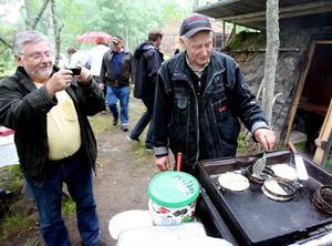Roland Olsson fotograderar när Göte Persson gör kolbullar som storleksbestäms med hjälp av ringar. Stekhällen är en av Eklundas avlagda.