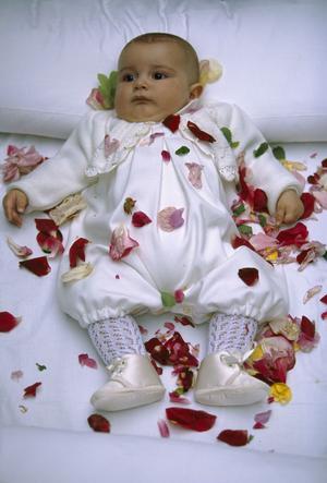 Ett barn bestrött med rosenblad under den årliga Fiesta del Colacho i norra Spanien. På fiestans sista dag blir de barn som fötts under året välsignade och skyddade mot ondska genom att figuren El Colacho hoppar över dem, varefter de beströs med blomblad.