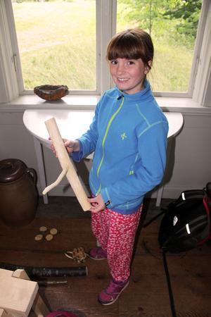 Sara Norrby visar sin klädhängare, på golvet syns också hennes näverkorg och början till en träbil.