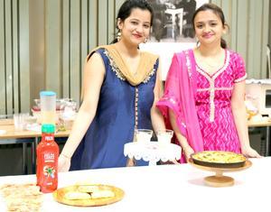 Name-Ashwini och Payal står vid ett av matborden som bjuder på delikatesser från Indien.