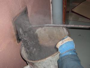Räddningstjänsten tömmer ut sot efter att ha släckt en soteld i en skorsten.