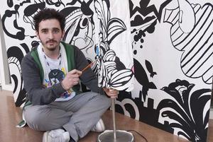 Talang. Arber Beqiri från medieprogrammet Wensnströmska gymnasiet är en multitalang inom grafisk design och formgivning. Han har ständigt nya projekt på gång. På bilden kan vi se hans väggmålning, lampan som han håller på att designa och hans egendesignade t-shirt föreställande Jackson Five. Foto: MIRANDA TARTAGLIONE
