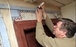Konservator Lennart Persson injicerar lim bakom dalmålningarna för att fästa tillbaka dem på väggen.FOTO: MIKAEL ERIKSSON