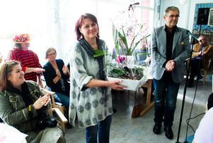 Vikarierande enhetschef Yvonne Norman tar emot blommor och gratulationer av omvårdnadsnämndens ordförande, Bengt-Olof Hedman.