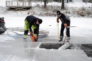 John Persson sågar till isblock som han och Tommy Nilsson forslar upp till islyktebyggarna.