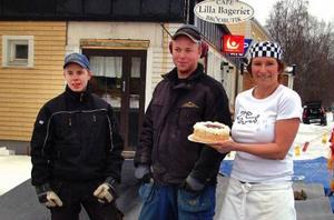 Snickarna Erik Nilsson, Bispgården, och Daniel Bergstedt, Hammarstrand, uppvaktas med extra gräddig fintårta av Lilla Bageriets i Stugun Sara Dahl som tack för den kommande efterlängtade nya fikytan.