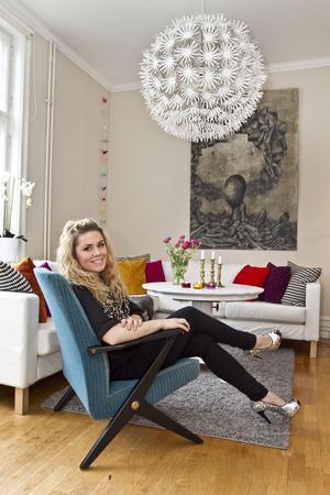 Sofie Källström trivs i loppisfåtölj från NK och glittriga skor. Tavlan i kol har hennes bror gjort.