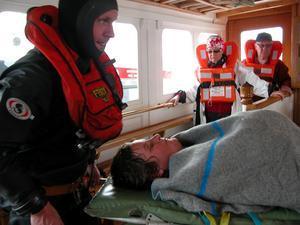 Bärs ut på bår. Räddningstjänsten bär ut en av de statister som spelar skadad under övningen.