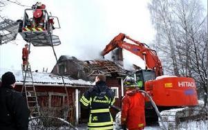 På förmmidagen revs taket och senare också skorstenen för att få stopp på branden.FOTO: MATS RÖNNBLAD
