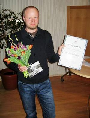 Anders Edvinsson med stipen- dium och blommor.