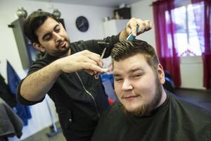 Charlei Calisar trimmar håret på Andreas Nordmark på barberarsalongen i Lit.