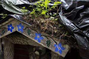Lennart gillade det färgglada. Han har dekorerat vindskivan med ganska grälla blommor. På stugans tak planterade han smultron och hallon.
