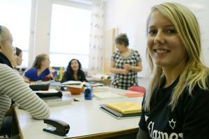 Ylva Skoglund går sista året på gymnasiet och har valt att läsa latin som en del av sin utbildning. I bakgrunden ser vi läraren Anna-Lisa Jonsson och några av de andra studenterna.
