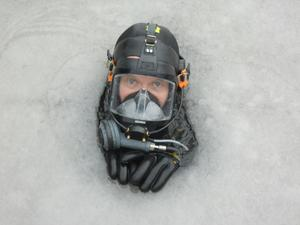 Räddningsdykare Stefan tittar upp i ett litet hål i isen, under en övning i hamnen.