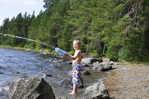 Femårige Love Moe testar vattengeväret vid en sandstrand ute på Andersön.