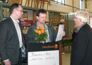 ( Foto: Per-Erik Edeborg ) Kennet Einars från Alfta Bike Park blev den första att få Eriksstipendiet i Ovanåker. Här tar han emot utmärkelsen av Thomas Larsson från Swedbank och Ulf Odenmyr, ordförande för Erikshjälpen i Edsbyn.