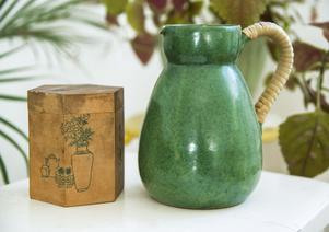 Den gröna tillbringaren är fyndad på samma loppis i Norrtälje som damejeannen. Träburken köpte Lina Lindbladh i Australien när hon bodde där och den används som teburk.