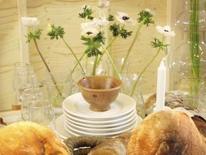 Vårigt och enkelt. Glas vitt, vitt proslin och kontrasterand grönska i mässans inspirationsutställning av Synnöve Mork. Rejält surdegsbröd är i linje med vurmen för omålat trä.