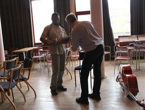 Sverker Åkered visar Abdi hur nyckelharpan fungerar.