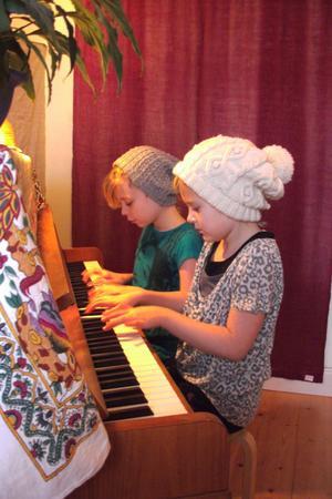 Freja och Ebba spelar fyrhändigt tillsammans med stor inlevelseoch koncentration.