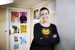Alveola Ämting, kulturarbetare, beskriver sig själv som aktivist, engagerad och virrig. I bakgrunden ser några av affischerna som hon har illustrerat.