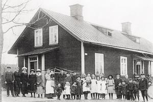 Dalavägen 15. Hyresgästerna samlade efter demonstrationståget  första maj 1914 framför den röda arbetarlängan. I huset fanns sex lägenheter om ett rum och kök.Trettiofem personer levde under samma tak. Edith är bara några månader gammal och sitter på mamma Lovisas arm, bredvid står fadern Adolf Wretman helgdagsklädd i vit skjorta.